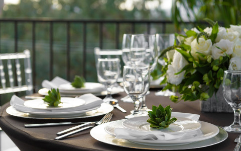 Close up of outdoor dining table with glasses, plates, and silverware