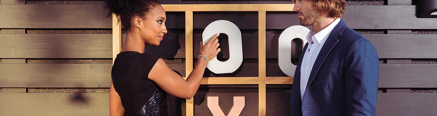 Woman holding a large O letter playing life size tic tac toe game