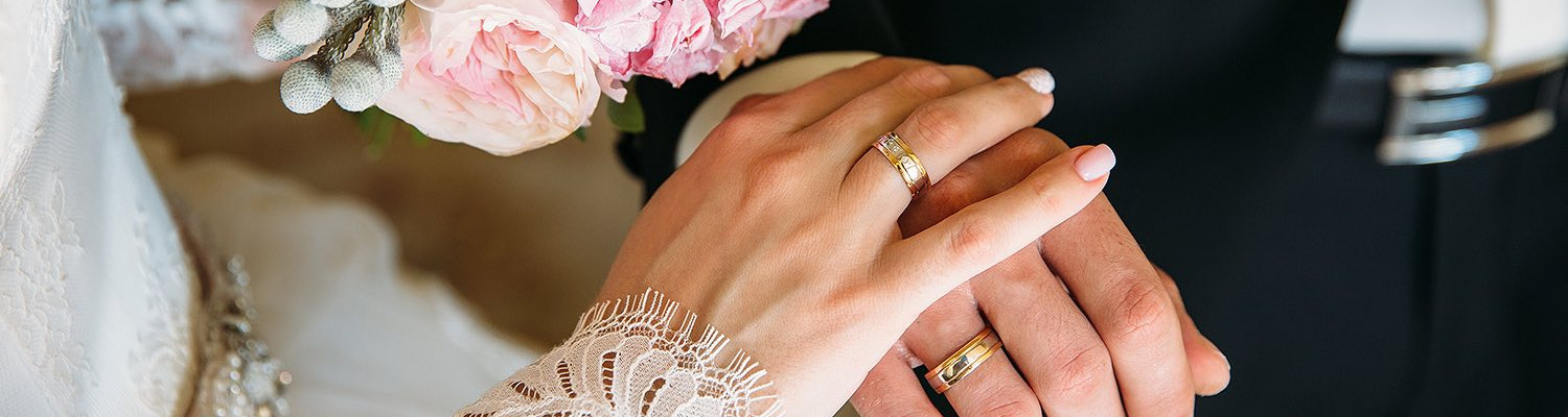 Close up of bride and grooms hands touching wearing wedding rings