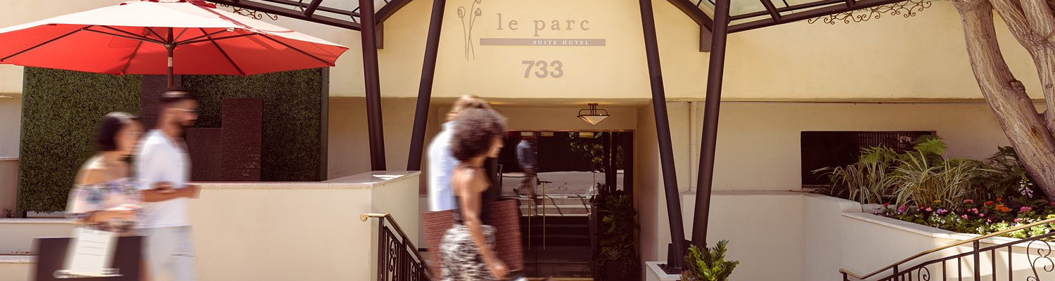 Couple walking outside entrance of Le Parc Suite Hotel