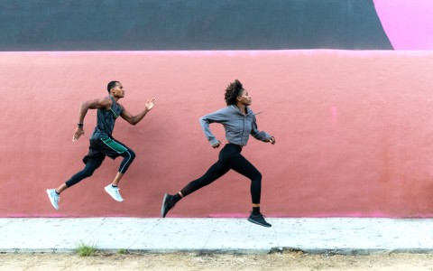 athletic runners leaping in front of urban wall
