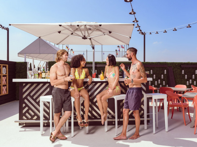 group of friends sipping cokctails hanging out at a rooftop bar and pool