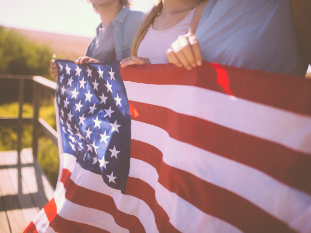 american flag being held by three people, green trees in the background