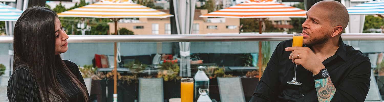 man and woman drinking orange mimosas on rooftop dining table