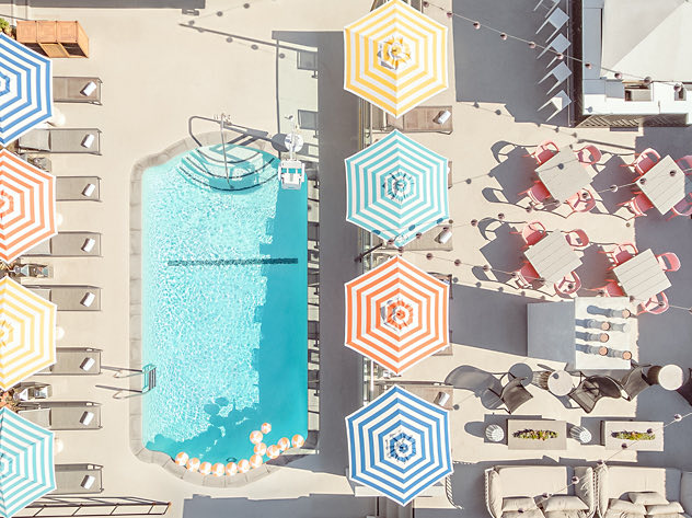 aerial view of rooftop pool and large striped umbrellas covering outdoor lounge furniture