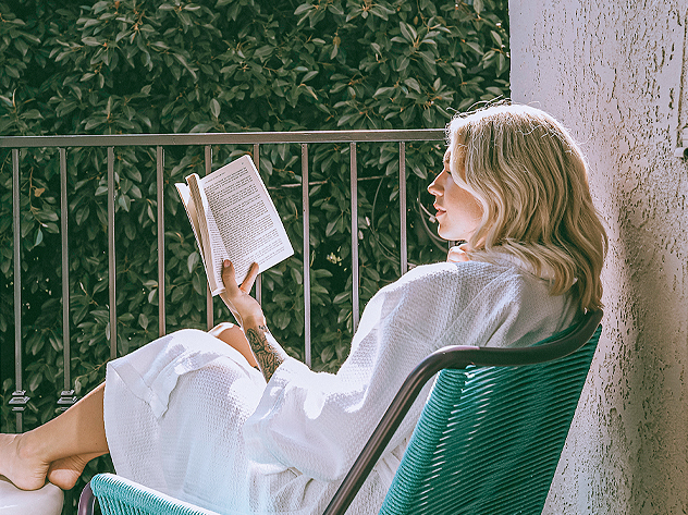woman sitting on blue patio chair wearing white robe and reading a book