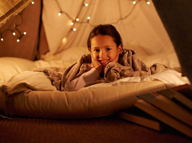 little girl in fort with string lights
