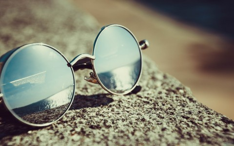 close up photo of round sunglasses resting on the ground with a reflection of the ocean