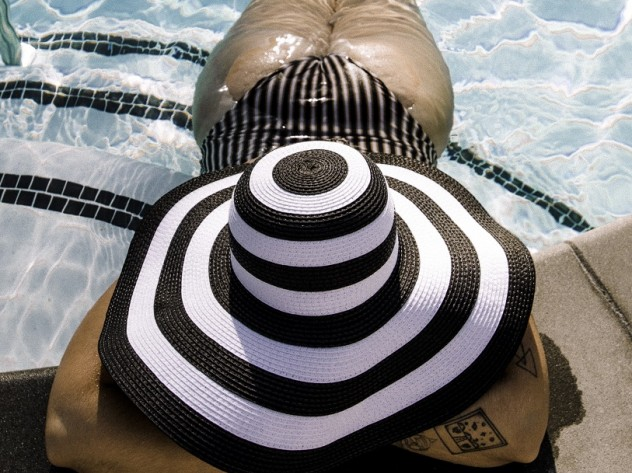 woman laying in pool face down with large black and white hat