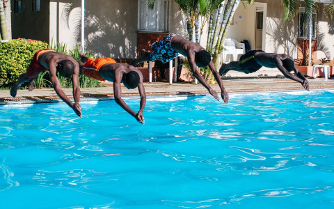 Four boys diving into pool