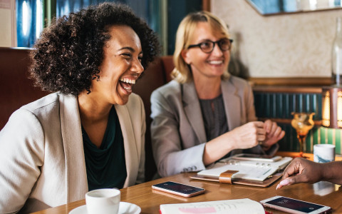 Two business women laughing at table