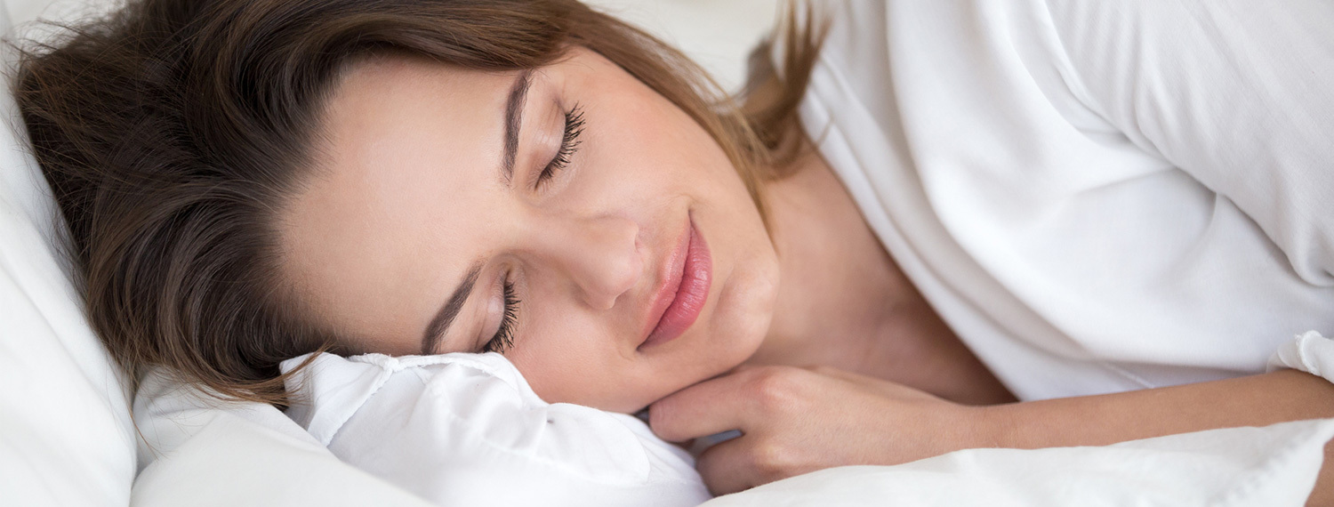 woman in bed with her head on a pillow and eyes closed