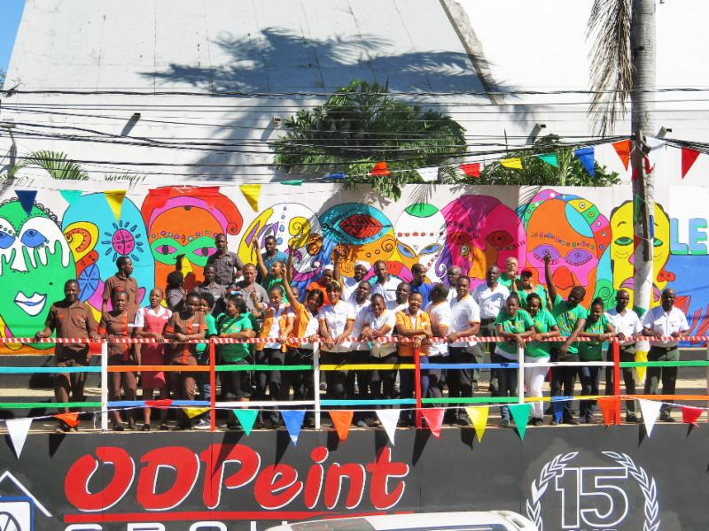 Group of people standing in front of colorful graffiti wall