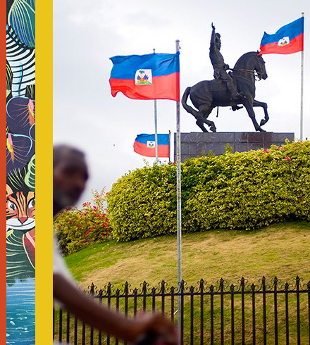 Steel statue of horse surrounded by Haitian flags
