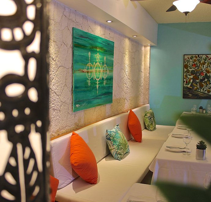 Dining area with white booth sitting area and colorful throw pillows