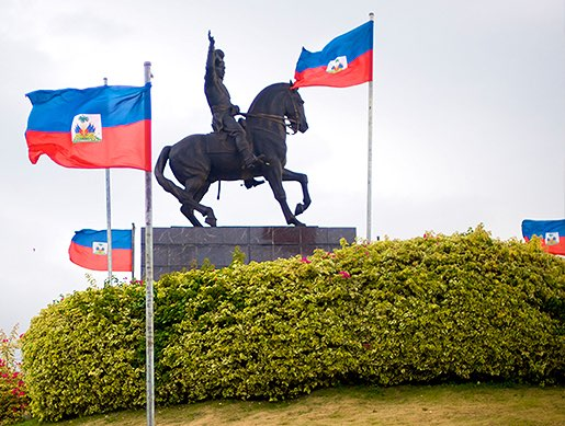 Steel horse statue surrounded by Haitian flags