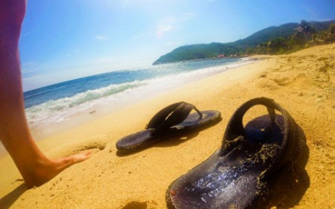 Person Stands Barefoot Beside a Pair of Discarded Sandals on a Golden Haitian Beach