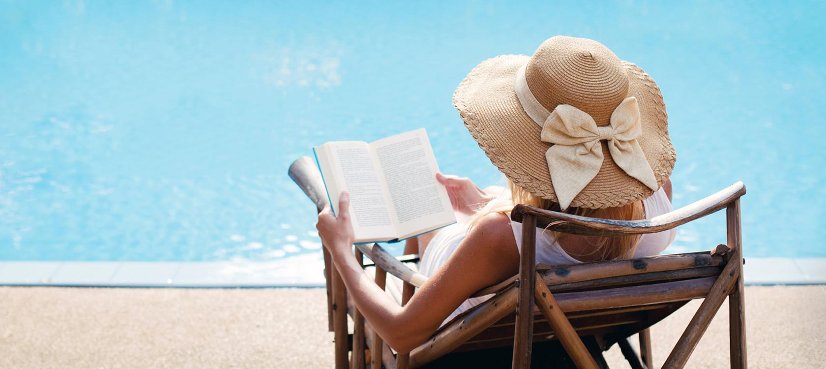 woman sitting by the pool reading a book