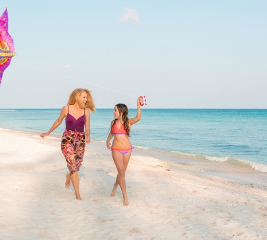 Mother and daughter fly a kite on the beach