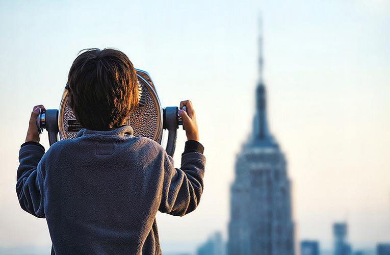 Tourist looking through a tourist viewfinder towards empire state building