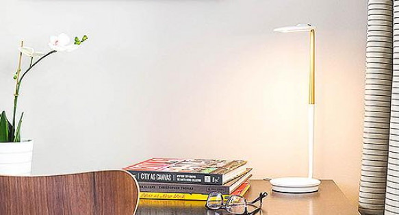 guest room wooden desk with books and white desk lamp
