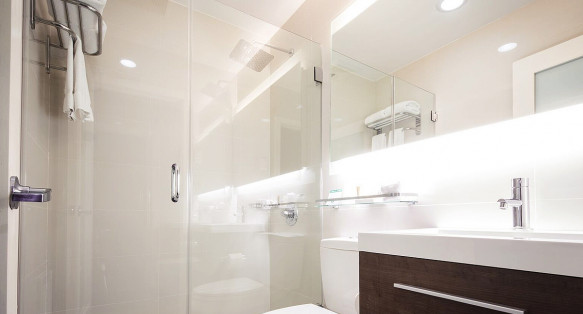view of the bathroom sink with cabinets and all white shower