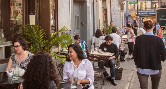 People sitting at restaurant tables on the sidewalk
