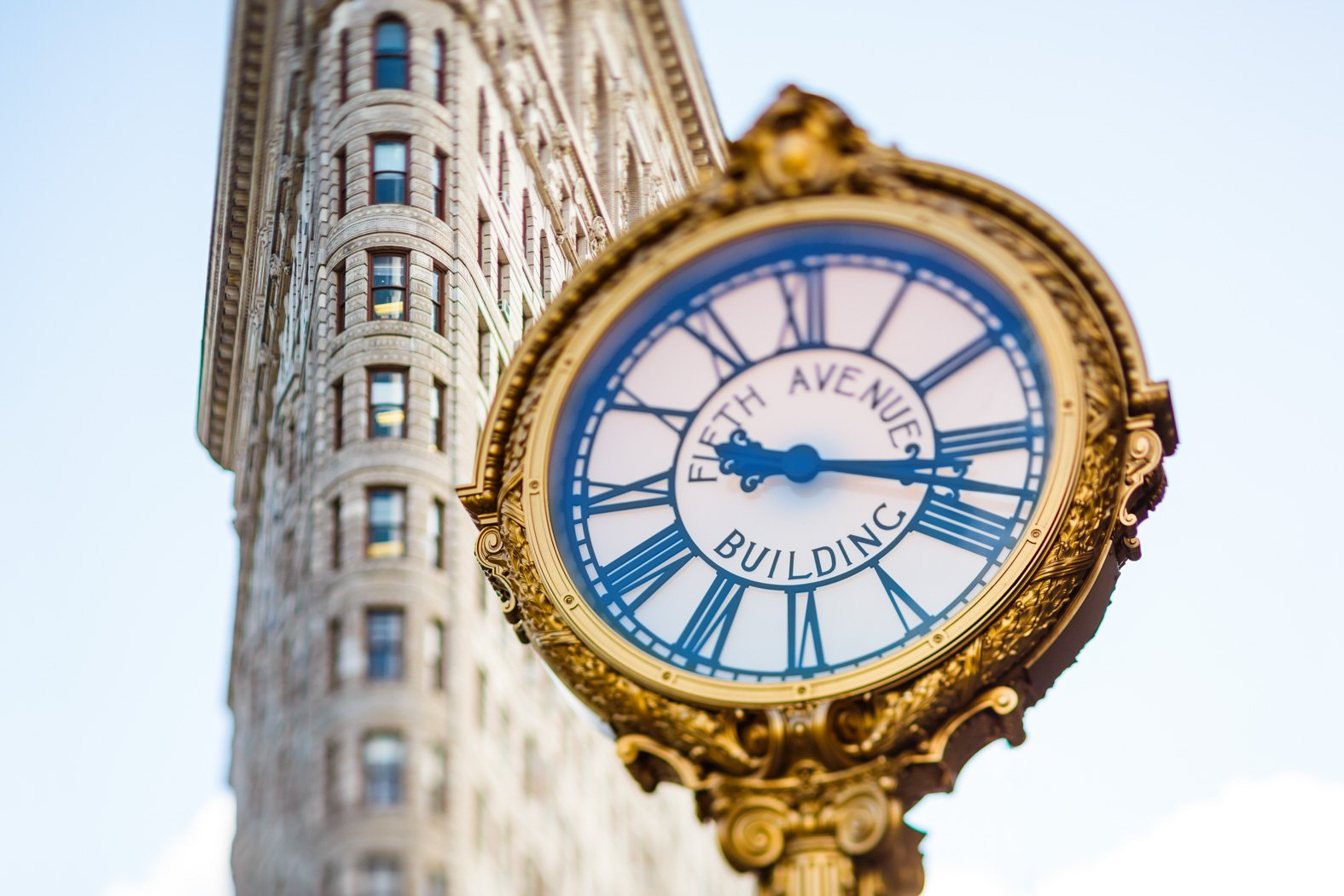 fifth avenue building clock with the flat iron building in the background