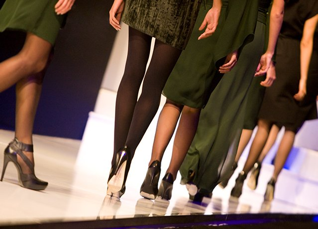 legs of models walking down a runway at a fashion show