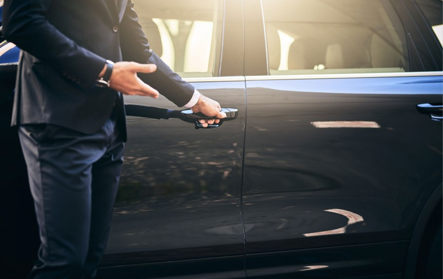 close up of man in a suit opening a car door