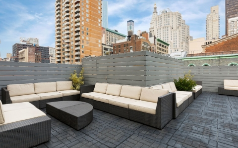 couches in rooftop lounge with view of city around