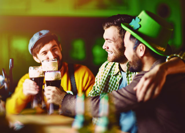 three friends drinking beer on st patricks day