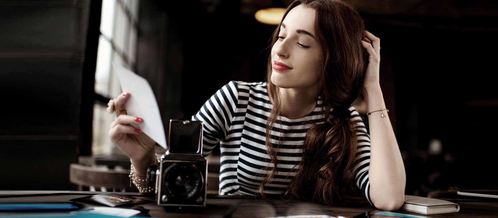 women wearing black and white stripped shirt, red lipstick. Sitting a in dark cafe with her vintage camera, admiring a photo
