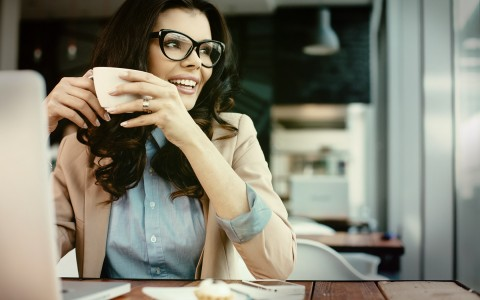 business women, sipping coffe in front of her computer contently looking out the window