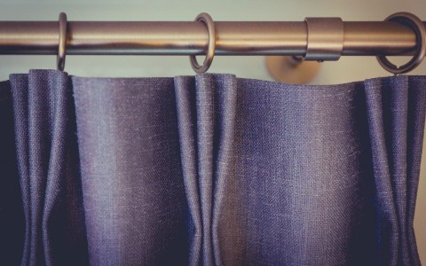 detail shot of grey curtains on bronze curtain rod