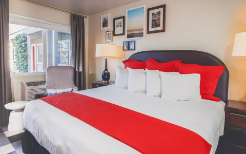 kind bed with white sheets and bright red pops of color from pillows and through blanket. Next to large window with ac unit. the wall decorated with collage of images