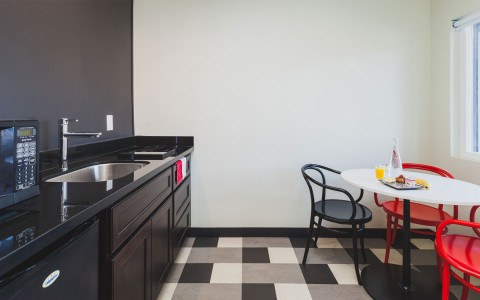 sleek black lacquer kitchenette with checkered carpet and cafe table with bright red and black chairs