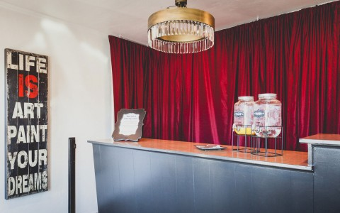 lobby desk with theater red drapes behind and retro chandelier