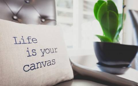 pillow with life is your canvas written on it. sitting on leather tufted chair next to table with plant