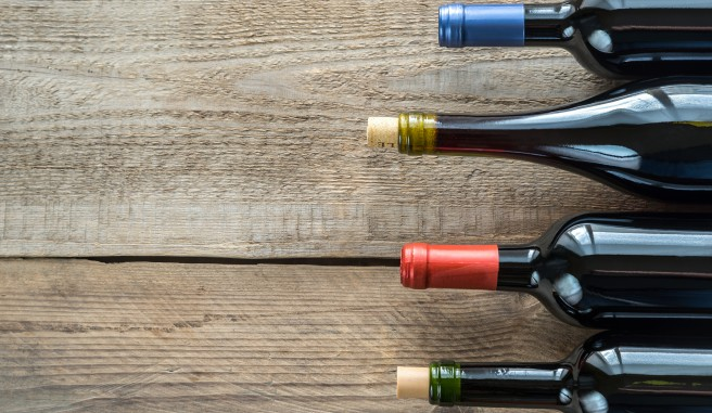 tops of wine bottles on a wooden table