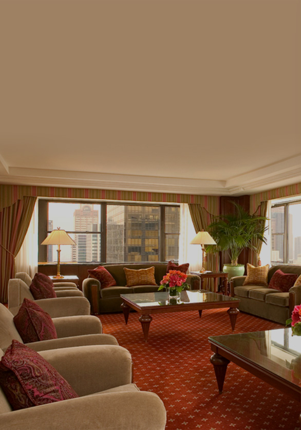 Towers Three Bedroom living room with beige couches with red accent pillows & new york city views