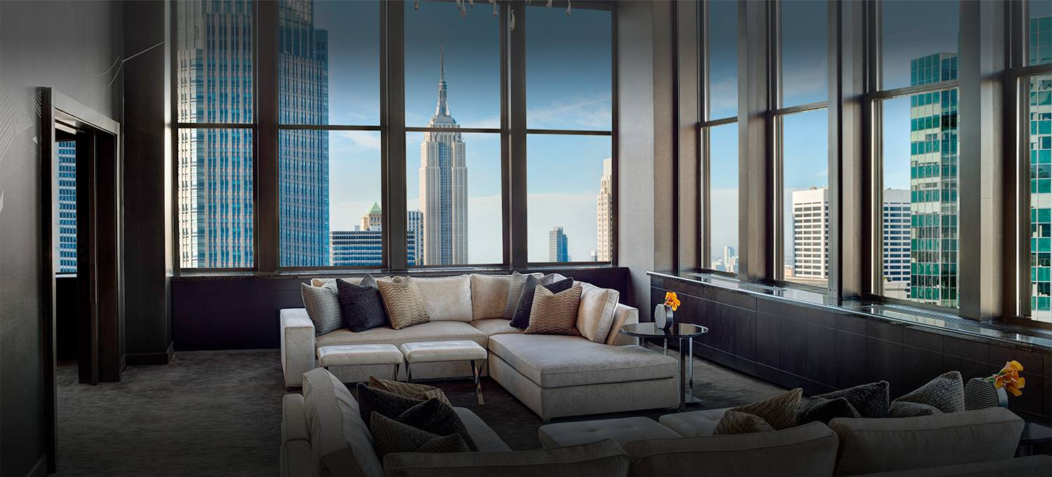 Champagne Suite living room with wall to ceiling views of new york city