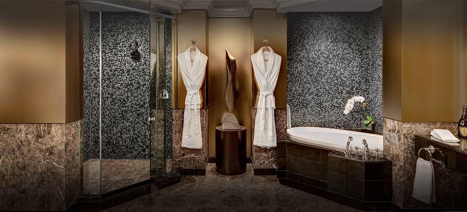 Champagne Suite bathroom features a walk-in shower, tub and terry cloth robes