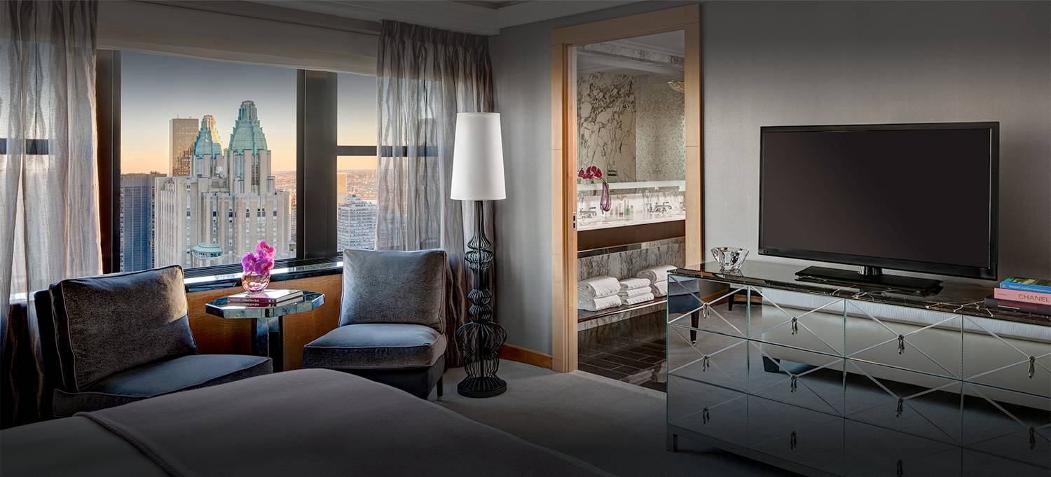 Jewel Suite bedroom with tv and sitting area with new york city skyline views