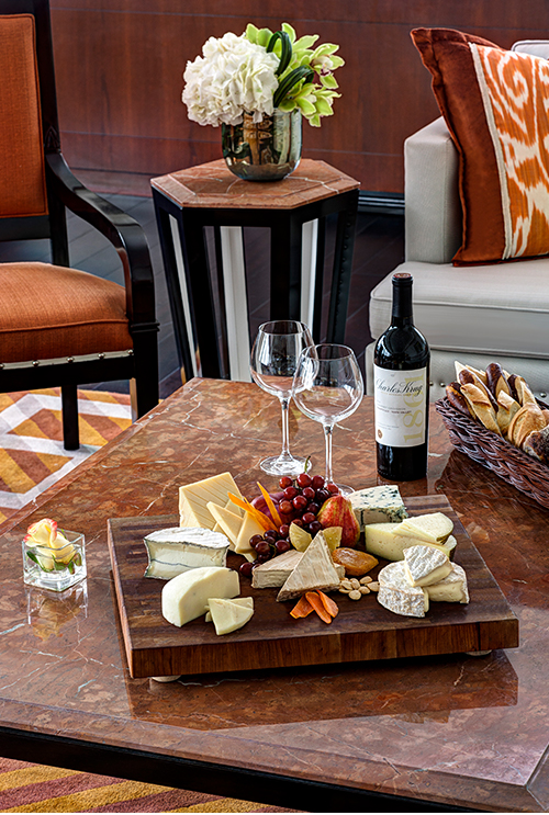 Cheese platter accompanied by wine and two wine glasses