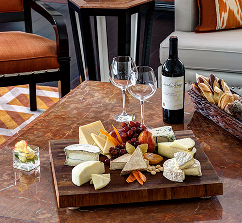 An assortment of cheeses on wooden board next to wine