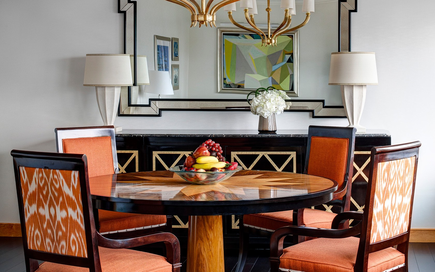 Wooden dining table with fruit arrangement   orange chairs. The Towers Rooms   Suites   NYC Hotels   Lotte New York Palace