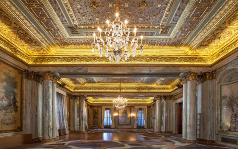 Elegant ballroom with marble columns, gold plated ceilings, chandelier & antique paintings