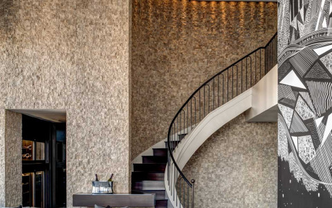 Champagne Suite staircase next to couch & modern black and white wall art