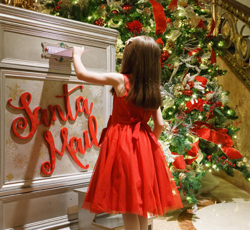 Girl in red dress inserting her santa mail
